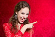 Portrait of a beautiful happy young woman pointing finger at