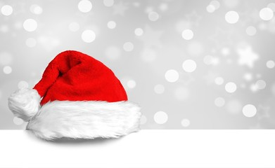 Weihnachtsmütze auf weißem Plakat mit schönem Bokeh