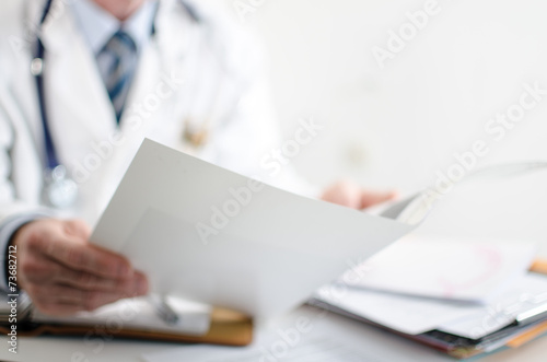 Doctor reading medical notes - 73682712