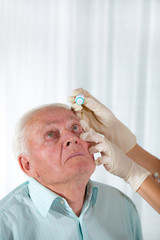 Doctor putting drops into a senior man's eyes