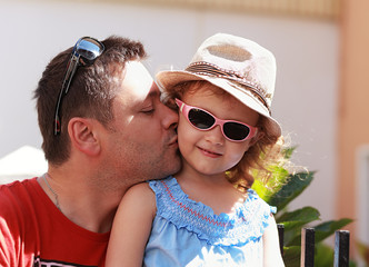 Happy father kissing his daughter in fashion pink glasses