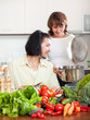 Young couple with fresh vegetables and greens in kitchen