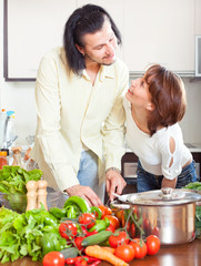 Psitive housewife with husbant cooking with fresh vegetables at