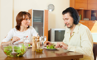 couple eating vegetables and herbs in the home