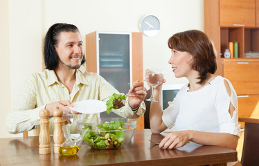 middle-aged couple eating vegetarian salad with water at home.