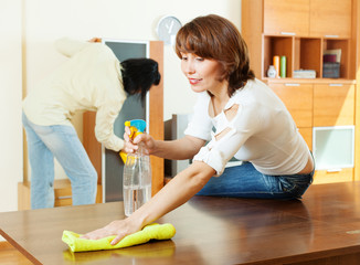 couple cleaning living room
