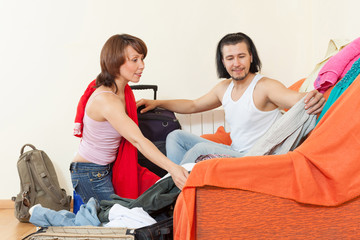 couple together choosing clothes for vacation