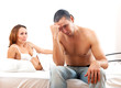 Sad man with problem in bed, woman consoling him on bed in bedro