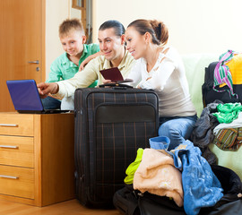 Three tourists packing luggage and reserving hotel in home