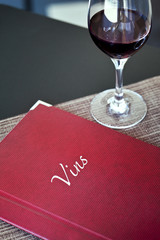 Wine list and glass of red wine in a French restaurant