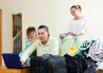 Family of three with teenager with luggage and reserving hotel f