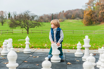 Adorable toddler boy playing with huge chess in a park