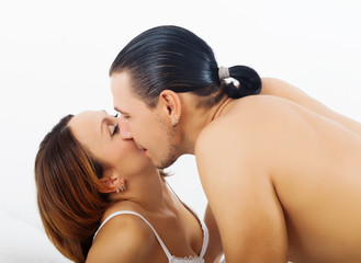 Loving couple kissing   in bed