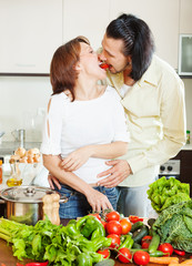 Flirting couple cooking together with  vegetables