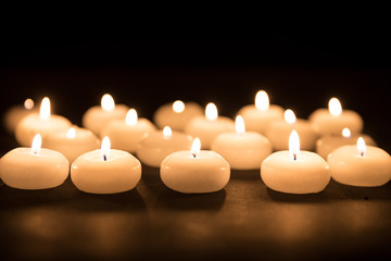 Several white candles with selective focus at a black background