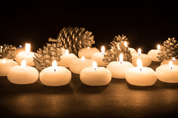 Burning candles with pine apples at a black background