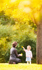 Mom and daughter walk in the rays of the autumn sun