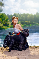 Beautiful girl with a Scottish Terrier in the Park