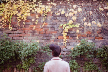 Young woman standing in front of a brick wall covered with ivy.