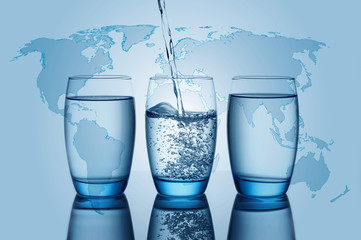 Water flowing and splashing into a glass with world map