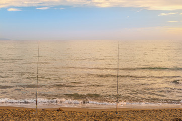 Beautiful sunset over the Tyrrhenian sea and two rods