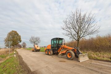 Strassenbau - Ein Grader und ein Walzenzug auf einer Strasse