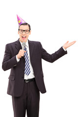 Businessman with party hat speaking on microphone