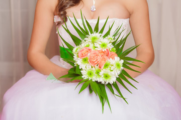 Bouquet of flowers in the hands of a young bride