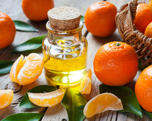 Bottle of essential citrus oil and ripe tangerines with leaves o