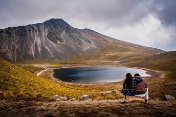 Couple hugging watching the mountain and lake