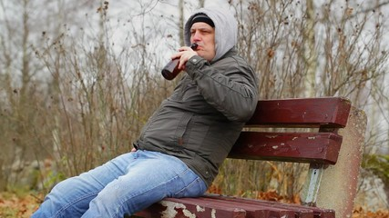 Man with beer bottle on the bench in autumn