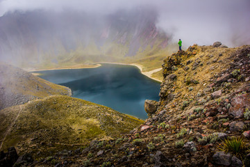 Hiker man watching a lake in a foggy mountain