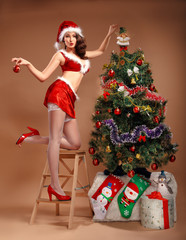 Girl in sexy suit of Santa Claus near the Christmas tree