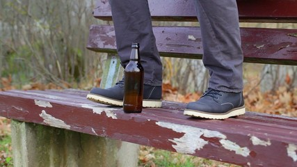 Beer bottle at a man's legs on the bench in the park