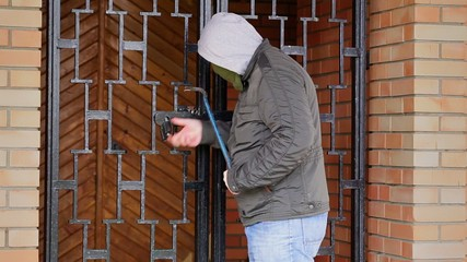 Robber with crowbar try to open gates