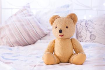 Vintage teddy bear sitting on Bed