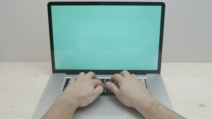 hands typing on notebook with green screen
