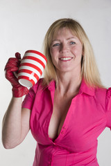 Woman in pink shirt holding a hot drink in a mug