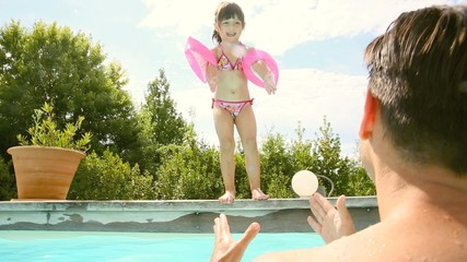Little girl with daddy in swimming pool