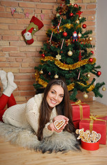 beautiful young woman with present boxes and cookies for Christm