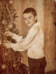 Child decorate on Christmas tree.
