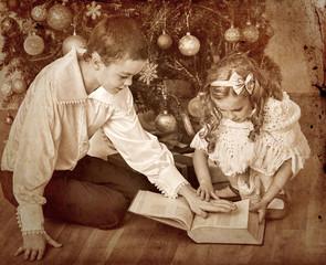 Children  receiving gifts under Christmas tree.
