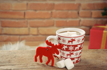 hot cocoa drink with sweet marshmallow on brick background