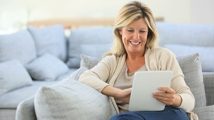 Mature woman websurfing on internet with tablet
