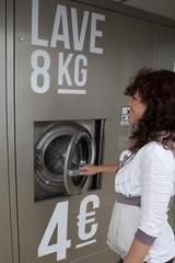 Femme devant une laverie automatique