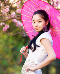 Young asian woman in the rays of the spring sun