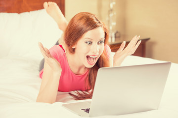 woman with arms raised using looking at her laptop screen
