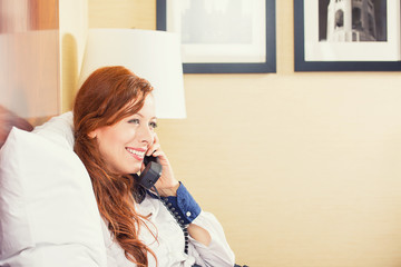 smiling businesswoman talking on phone sitting on bed in hotel