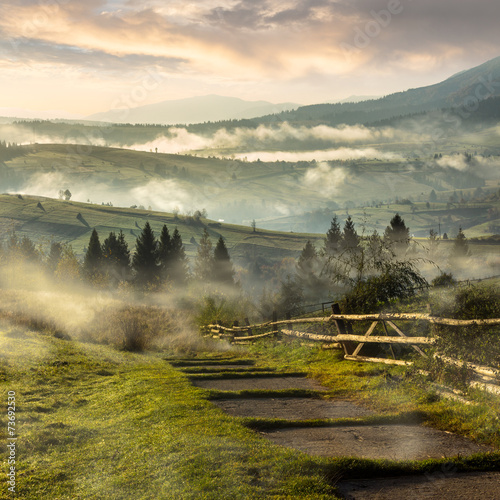 steps down to village in foggy mountains at sunrise - 73692530