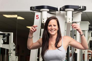 lächelnde Frau an einem Fitness-Gerät im Fitnessstudio